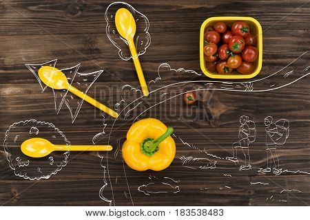 Brighten emotions. Yellow bell pepper lying on the wooden table near spoons and bowl with tomatoes