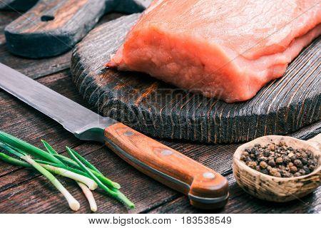 Raw pork meat loin on rustic wooden cutting board, green onions and peppercorns on old dark wood table. Close-up angle view
