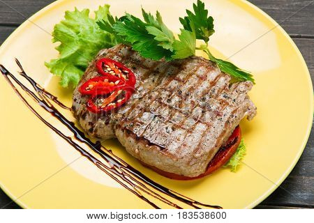Grilled beef steak with vegetables and parsley, closeup. Appetizing meat dish served with sauce, dinner meal.