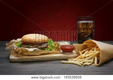 Fast food dish. Meat burger and potato chips and cola drink on wood at red background. Restaurant meal