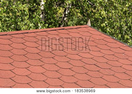 Roof with red bitumen shingles, trees in the background