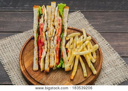 Fast food meals, sandwich and french fries. Potato chips, lunch snack on wood