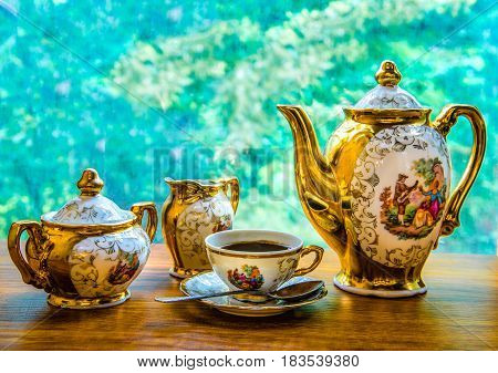 On the background of green foliage elegant coffee service : teapot sugar bowl milk jug and coffee Cup. On all objects of the drawing depicting a love scene in a medieval style.