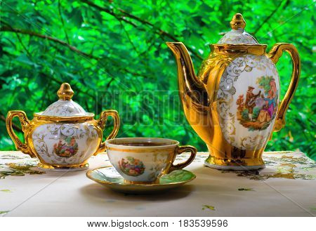 On the background of green foliage is graceful coffee set of three pieces: teapot sugar bowl and coffee Cup. On all objects of the drawing depicting a love scene in a medieval style.