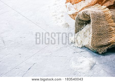 Packs of flour and sugar pile on the concrete background. Close up. Space for your text or logo