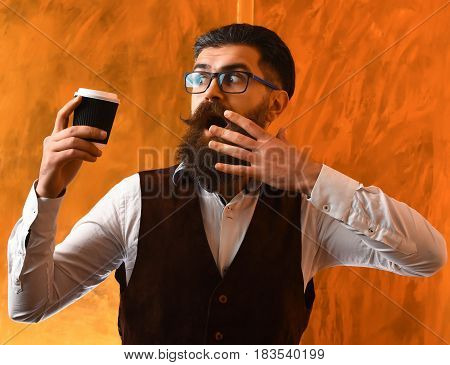 Bearded man long beard. Brutal caucasian unshaven surprised hipster with glasses and moustache holding black plastic coffee cup or mug on brown studio background