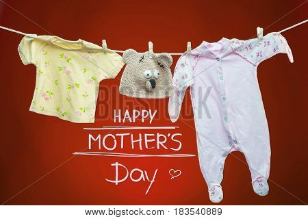 Baby goods hanging on the clothesline on red background. Happy mothers day concept