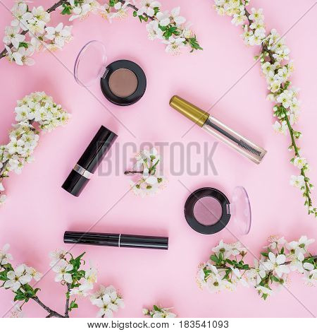 Feminine desk with cosmetic - lipstick, shadows, mascara and white flowers on pink background. Flat lay, top view.