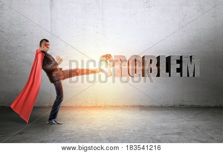 A businessman in a red cape and a mask beating a concrete 'Problem' writing with his leg. Business and success. Overcoming difficulties. Achievement and results.