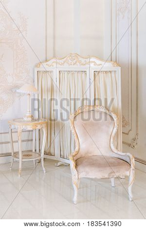 Luxury bedroom in light colors with mirror and folding screen. Elegant classic interior.
