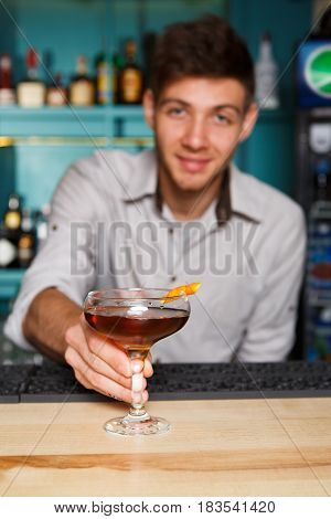 Young handsome Barman offers alcohol cocktail in night club. Professional male bartender at work in bar made a drink for party. Focused on glass
