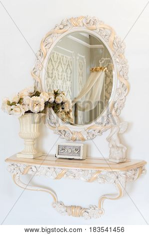 Luxury bedroom wall in light colors with mirror. Elegant classic interior.