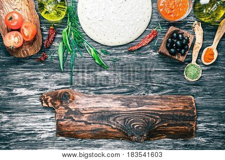 Pizza ingredients - round dough base, fresh tomatoes, sauce, olive oil, green herbs and spices on background of black textured wood. Rustic signboard as frame. Top view