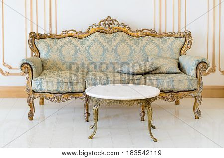 Luxury livingroom in light colors with golden furniture details. Elegant classic interior.