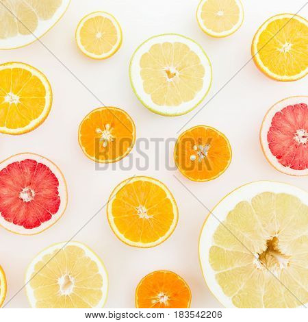 Fruit background. Sliced citrus fruits on white background. Flat lay, top view.