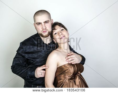 Man and woman hugging on a gray background