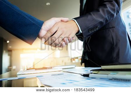 Two businessmen shaking hands during a meeting in the office success dealing greeting & business partner concepts - soft light.