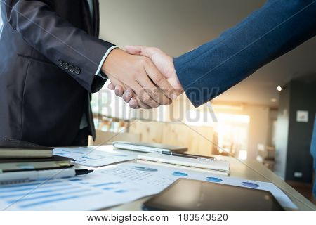 Two businessmen shaking hands during a meeting in the office success dealing greeting & business partner.