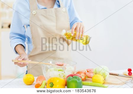 Close up of Asian girl garnishing salads in the kitchen with others garnishing their salads and oil pouring into bowl of salad