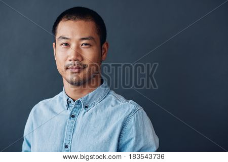 Portrait of a casually dressed young Asian designer smiling confidently while standing against a gray wall in an office