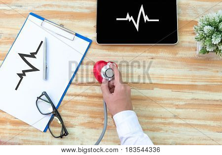 The doctore with a medical stethoscope check heart near a laptop on a wooden table