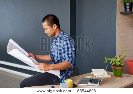 Casually dressed confident young Asian architect leaning on a desk focused on reading blueprints while working in a modern office