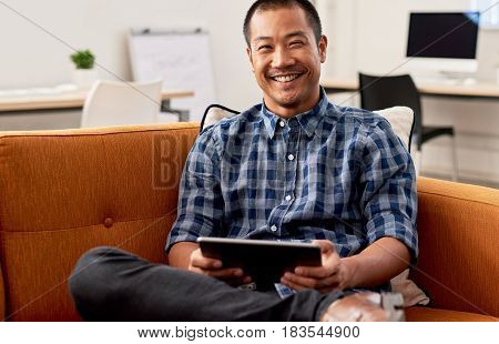 Portrait of a young Asian designer working online with a digital table while sitting alone on a sofa in a large modern office