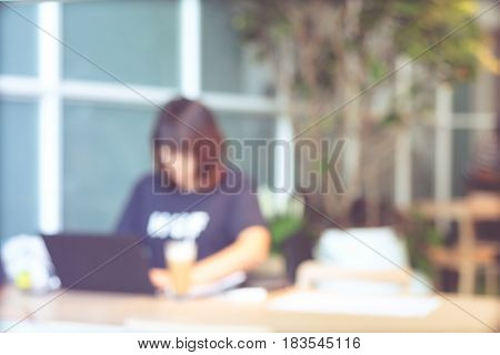 Blurred background Blur woman using with lap-top computer at coworking space in casual style