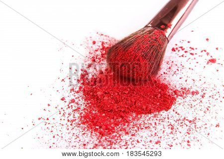 Makeup brush closeup with red blush sprinkled on white. Make up and female cosmetics background