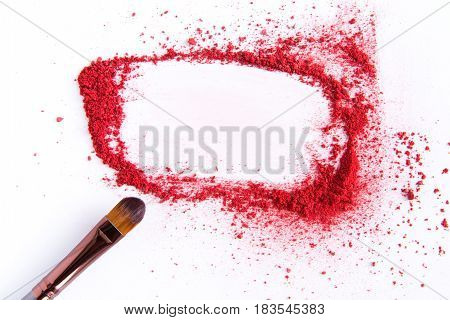 Makeup brush frame background with eyeshadow of red tone sprinkled on white. Make up and female cosmetics background