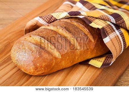 Traditional Russian wheat bread wrapped in a towel closeup