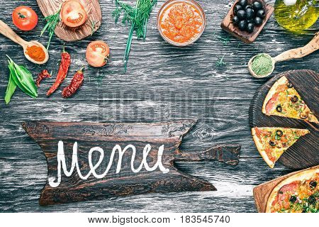 Baked pizza and ingredients -fresh tomatoes, sauce, olive oil, green herbs and spices on background of black textured wood. Cutting board with text 'Menu'. Top view