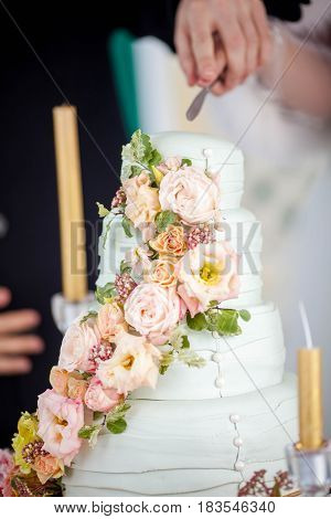 the bride and groom cut the beautiful white wedding cake with fresh flowers