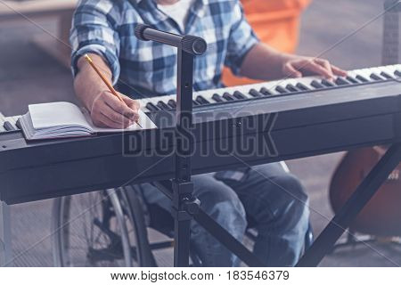 Enjoying my hobby. Gifted young skilled handicap sitting in the wheelchair in the studio and enjoying free time while playing the piano and whiting notes