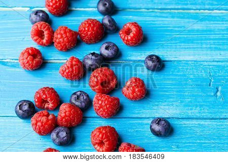 Raspberry and blueberry Closeup on blue wooden table