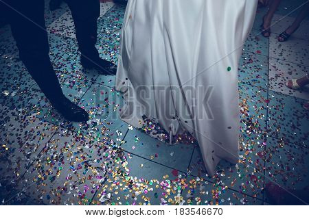 the bride and groom are dancing on a background of confetti