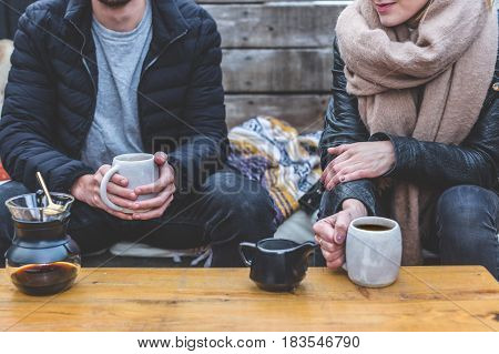Man and woman sitting outside at a wooden table with coffee mugs, a french press and milk.