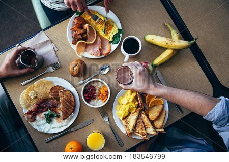 Three people at table with breakfast, view from above.