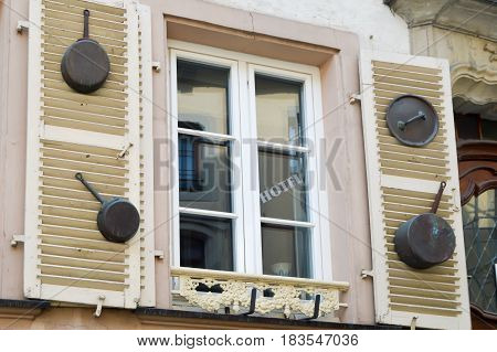 Windows with shutters and poelons hang on in front of a restaurant in the Grand Duchy of Luxembourg