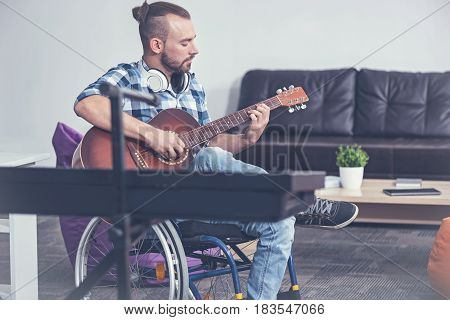 Full of concentration. Involved talented young handicap sitting on the wheelchair in the studio and enjoying playing guitar while having alternative therapy session