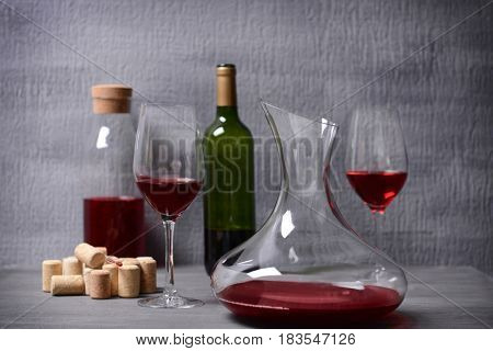 Decanter and glasses with red wine on table against gray background