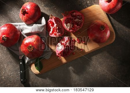 Wooden board with pomegranates on gray background