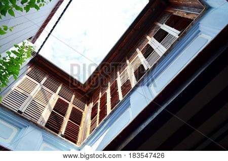 Blue airy terrace with brown wooden window on the second floor bottom view - architecture concept