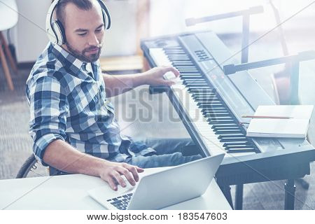 Recording song in details . Talented experienced professional musician sitting on the wheelchair in the studio and playing musical instrument while performing and recording a song
