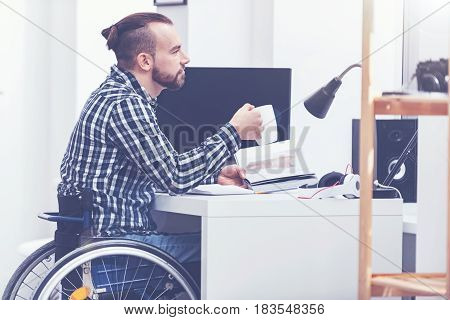 Dreaming about joyful future. Inspired relaxed young handicap sitting on the wheelchair in the studio and relaxing while reading book and drinking coffee