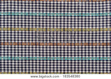 the textured background of checkered fabric or textile material with color strips