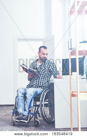 Looking for inspirational quotes. Handsome smart young handicap sitting on the wheelchair indoors and relaxing while reading book and making notes