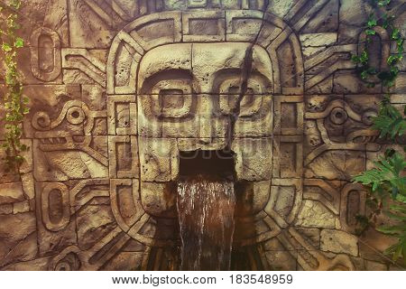 Ancient civilization image of a man in a rock. Ancient artwork on a rock. The head carved from a stone. Water flows from the mouth. Ancient Sumerians, Aztecs, Incas. The pagan treasure of the Gods.