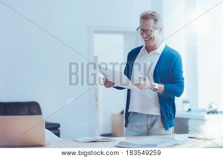 Like my work. Cheerful delighted man holding papers and working on the project in the office