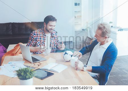 Football fan. Cheerful delighted colleagues sitting in the office and having a break while drinking coffee